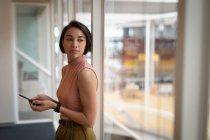Вид сбоку на вдумчивую азиатскую бизнесвумен, держащую свой мобильный телефон, глядя в окно в офисе — стоковое фото