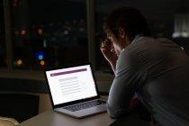 Вид сбоку красивый молодой мужской исполнительной работы в ноутбук на стол в современном офисе — стоковое фото