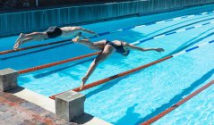 Side view of male and female Caucasian swimmers jumping into water in the same time at the swimming pool in the sunshine — Stock Photo