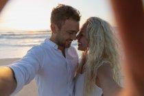 Vista frontal de la joven pareja de amor avergonzándose mientras están de pie en la playa. Están disfrutando de sus vacaciones - foto de stock