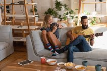 Front view of Woman using mobile phone while mixed race man playing guitar in living room at home — Stock Photo