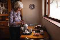 Side view of an active senior woman pouring coffee in a cup at dining table in kitchen at home — Stock Photo