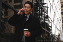 Front view of young well dressed Asian businessman with disposable coffee cup talking on mobile phone in city — Stock Photo