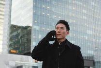 Vista basso angolo di giovane uomo d'affari asiatico che parla sul telefono cellulare mentre in piedi sulla strada con la costruzione dietro di lui in città — Foto stock