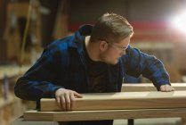 Side view of carpenter taking measurement of wood at workshop — Stock Photo