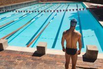 Rear view of young Caucasian male swimmer standing at the edge of outdoor swimming pool on sunny day — Stock Photo