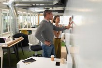 Vista laterale multi etnica della gente di affari che discute sopra una cianografia contro un muro in ufficio — Foto stock
