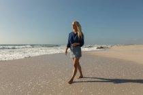 Vue de face de la femme blonde debout à la plage par une journée ensoleillée. Elle marche. — Photo de stock