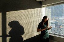 Vista frontal de la joven mujer trabajo Ejecutivo en tableta digital junto a la ventana de una oficina moderna - foto de stock