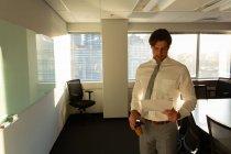 Фронтальний вид молоді чоловіки виконавчий чашкою ароматної кави читання документів у сучасному офісі — стокове фото