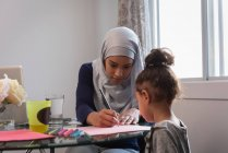 Front view of mixed race mother wearing hijab teaching her daughter at home around a table — Stock Photo