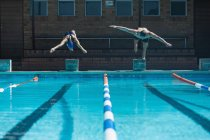 Front view of male and female Caucasian swimmers jumping into water in the same time at the swimming pool in the sunshine — Stock Photo