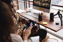 Vista ad alto angolo di diversi uomini d'affari che discutono sulla fotocamera digitale in ufficio — Foto stock