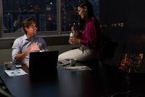 Vista frontale di giovani dirigenti d'ufficio multietnici felici che parlano tra loro mentre mangiano a tavola in un ufficio moderno — Foto stock