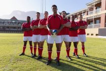 Front view of a team of male multi ethnic rugby players standing with a rugby ball in the rugby ground on a sunny day — Stock Photo