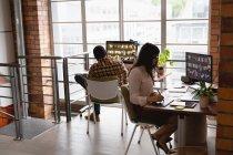 Vista laterale della donna d'affari caucasica che lavora su tablet grafico mentre l'uomo afro-americano lavora dietro di lei in ufficio — Foto stock