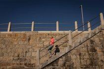 Низкий угол обзора активной пожилой женщины, спускающейся по лестнице по набережной рядом с пляжем под солнцем — стоковое фото