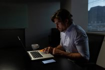 Vista laterale del giovane dirigente di sesso maschile seduto a tavola e che lavora su laptop in un ufficio moderno — Foto stock