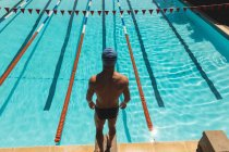 High angle view of young Caucasian male swimmer standing on starting block at swimming pool in the sunshine — Stock Photo