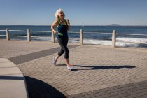 Front view of an active senior woman doing jogging on a promenade along the sea under the sunshine — Stock Photo
