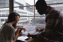 Взгляд со стороны различных деловых людей, обсуждающих за чертежом в офисе за столом — стоковое фото