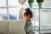 Vista lateral da pequena garota parada em casa em pose triste — Fotografia de Stock
