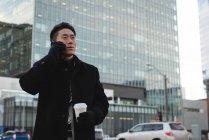 Vista laterale del giovane uomo d'affari asiatico che parla al telefono cellulare mentre tiene un caffè in mano con la costruzione dietro di lui in città — Foto stock