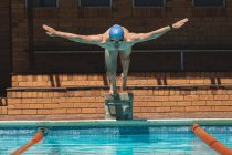 Front view of young Caucasian male swimmer with arms stretched out diving into outdoor swimming pool on sunny day — Stock Photo