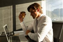 Side view of handsome young male executive having coffee while working on laptop at table in a modern office — Stock Photo