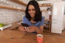 Frontansicht einer lächelnden Frau, die ihr Handy zu Hause in der Küche benutzt — Stockfoto