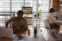 Vista frontale di diversi uomini d'affari che lavorano su laptop in ufficio — Foto stock