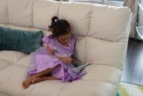 Vista de ángulo alto de la chica de raza mixta utilizando tableta digital en la sala de estar en casa - foto de stock