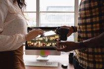 Section médiane des gens d'affaires discutant sur tablette numérique et appareil photo dans le bureau — Photo de stock