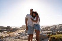 Angolo di vista basso della coppia afro-americana rilassante e in piedi sulla roccia vicino al mare — Foto stock