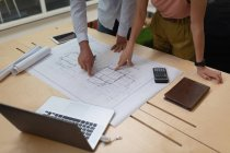 Mid section of business people standing in the office and discussing over a blueprint on the desk — Stock Photo
