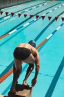 High angle view of male Caucasian swimmer standing on starting block in starting position at swimming pool in the sunshine — Stock Photo