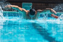Front view of a male swimmer with swim goggle swimming the butterfly at the swimming pool — Stock Photo