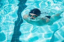 Front view of young Caucasian male swimmer emerging from water in outdoor swimming pool on a sunny day — Stock Photo