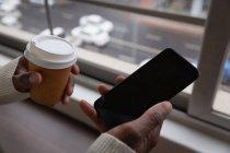 Крупним планом бізнесмен, за допомогою мобільного телефону і чашки кави в кожному руки в офісі їдальня — стокове фото