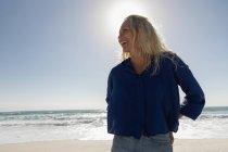 Вид спереди красивой блондинки, улыбающейся, стоя на пляже в солнечный день. Она улыбается. — стоковое фото