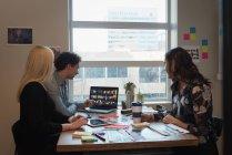 Vue latérale des gens d'affaires discuter au sujet des photos sur l'ordinateur portable au bureau — Photo de stock