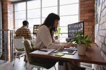 Vista laterale della donna d'affari caucasica che lavora sul laptop mentre l'uomo afro-americano lavora dietro di lei in ufficio — Foto stock
