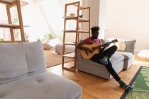 Side view of African american Man sitting and playing guitar in living room at home — Stock Photo