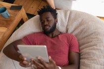 Visão de alto ângulo do homem afro-americano usando tablet digital na sala de estar em casa — Fotografia de Stock