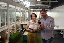 Vista frontal de gente de negocios multiétnicos de pie en la oficina mientras discute sobre su teléfono móvil - foto de stock