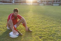 Front view of a thoughtful male Caucasian rugby player sitting with rugby ball in the ground — Stock Photo