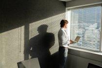 Vista lateral de belo jovem executivo masculino com laptop olhando através da janela em um escritório moderno — Fotografia de Stock