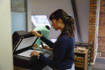 Vista laterale di una donna d'affari premurosa che utilizza la macchina Xerox in ufficio — Foto stock