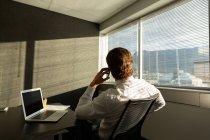 Rückansicht junger männlicher Führungskräfte, die in einem modernen Büro am Tisch sitzen und mit dem Handy sprechen — Stockfoto