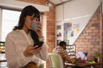 Front view of business woman using mobile phone while having cup of coffee in office — стоковое фото